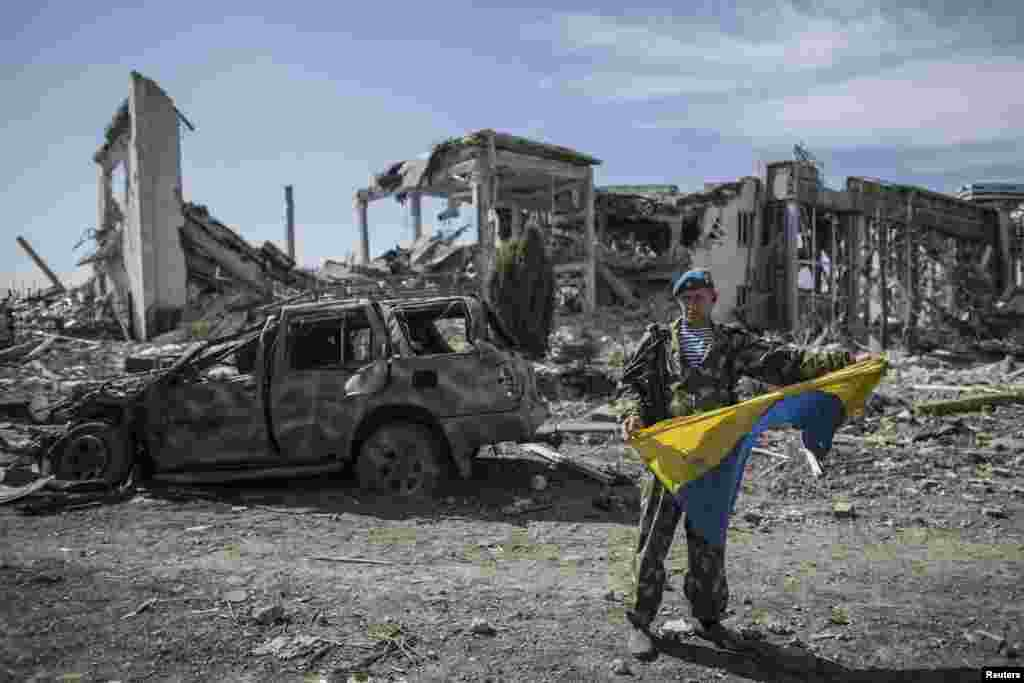 A pro-Russian rebel displays a captured Ukrainian flag at the destroyed airport in Luhansk. (Reuters/Marko Djurica)