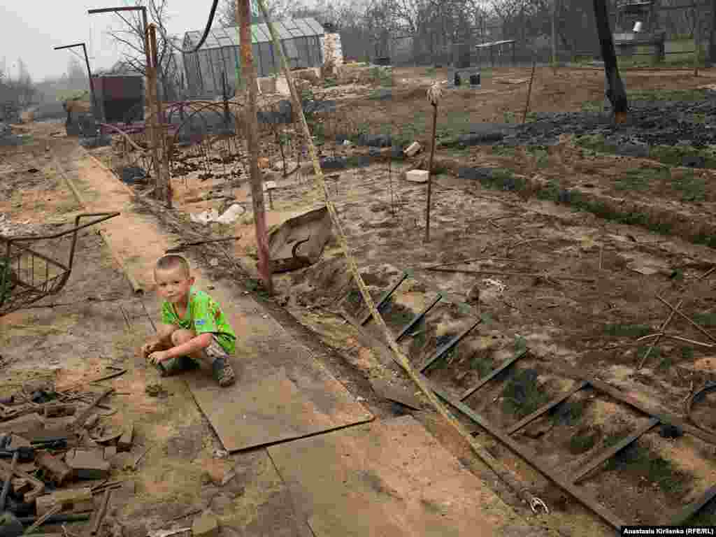 Lyosha barely cried when his family fled from the fire, says his mother. The photo shows the remains of their house in Borkovka.