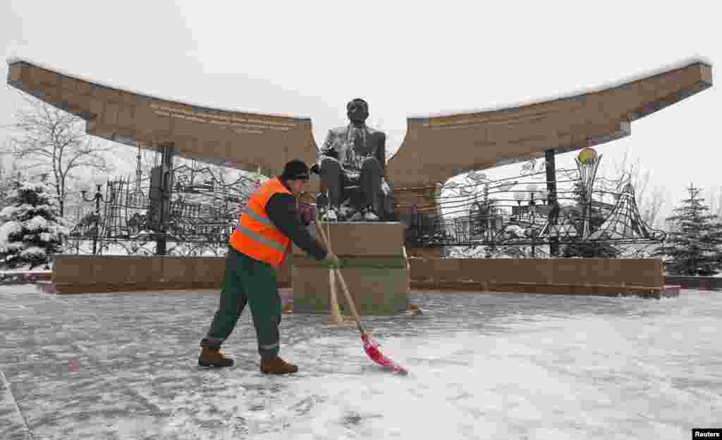 A worker removes snow in front of a statue of President Nursultan Nazarbaev at the Park of the First President on the eve of the Day of the First President in Almaty.
