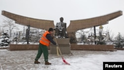 A worker removes snow in front of a statue of President Nursultan Nazarbaev in Almaty.