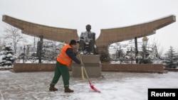 Дворник убирает снег рядом с памятником первому президенту Нурсултану Назарбаеву. Алматы, 30 ноября 2012 года.