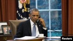 Barack Obama duke folur me telefon në zyrën e tij