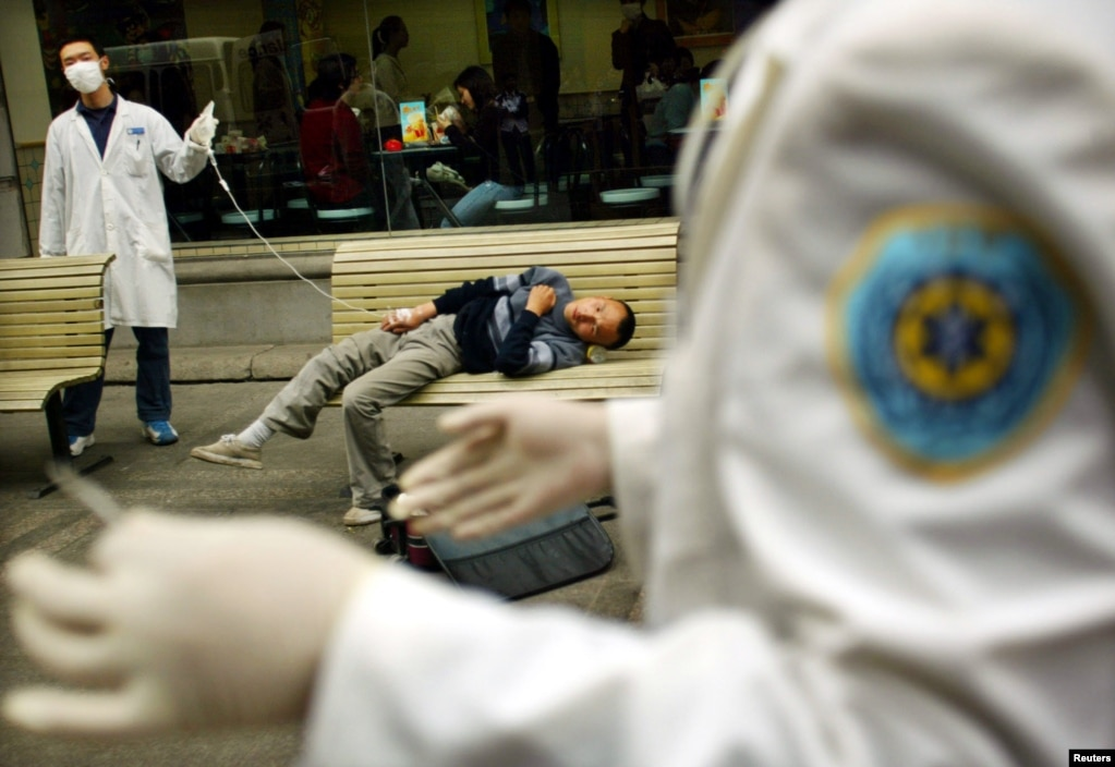 Қытайдың Ухань қаласында есінен танып құлаған адамның қасында тұрған дәрігерлер. Науқас атипиялық пневмония (SARS деген атаумен белгілі) жұқтырған болуы мүмкін.