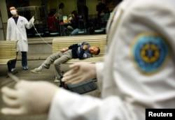 Медики в Ухане рядом с упавшим в обморок пациентом, предположительно заразившимся атипичной пневмонией (заболевание известно как SARS – тяжелый острый респираторный синдром).