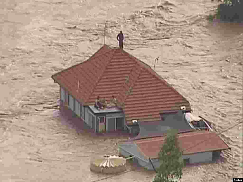 People are seen on the rooftop of a house in Grantham, a township between Toowomba and Brisbane, in this still image taken from video January 10, 2011. Tsunami-like flash floods raced towards Australia's third-largest city of Brisbane on Tuesday, prompting evacuations of its outskirts, flood warnings for the financial district and predictions that the death toll is likely to climb. REUTERS/Nine Network via Reuters TV (AUSTRALIA - Tags: ENVIRONMENT DISASTER) AUSTRALIA OUT.