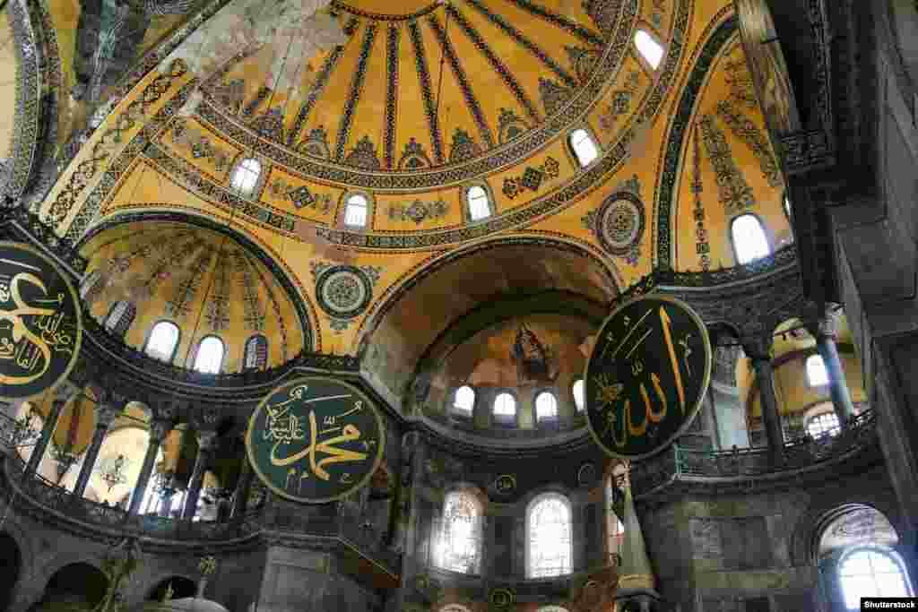 Un mozaic (centru) creștin în mijlocul discurilor care prezintă numele liderilor islamici timpurii și celebre învățături musulmane. Odată cu transformarea clădirii în muzeu de către Ataturk, Hagia Sophia a devenit un simbol al Turciei seculare și al conviețuirii religioase.