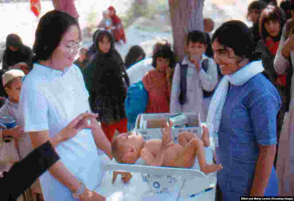 A child being measured and weighed in a village clinic. The woman on the left is an American Peace Corps nurse working with an Afghan student nurse (right).