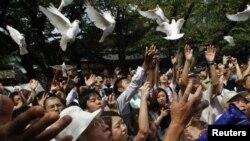 Njerëzit i lirojnë pëllumbat në tempullin kundërthënës Yasukuni