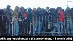 Трудовые мигранты стоят в очереди в миграционном центре в Сахарове.