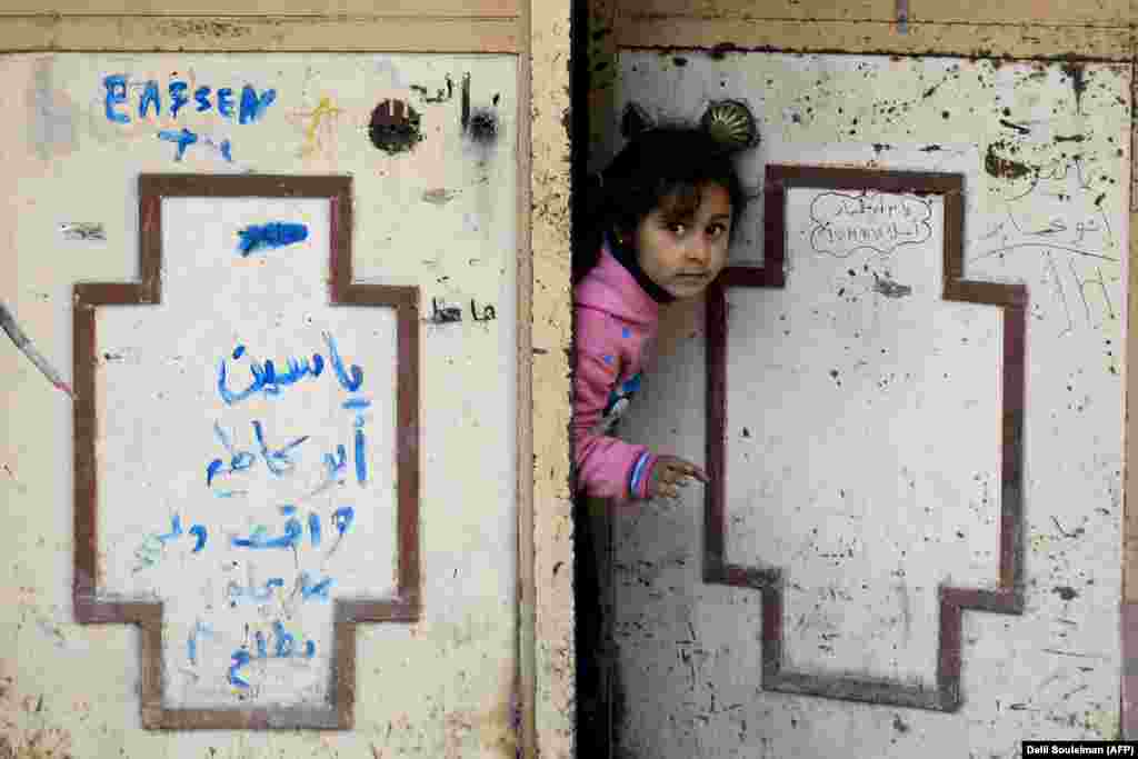 A girl peers through a door in Syria's devastated city of Raqqa. (AFP/Delil Souleiman)