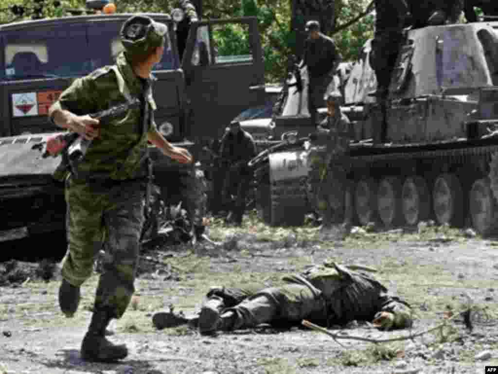 11 августа грузинские войска, выбитые из Цхинвали, попытались закрепиться в Гори, но вскоре отошли, чтобы защищать Тбилиси. Ожидалось, что рсосийские войска начнут наступать на столицу Грузии. На фото российский военный пробегает мимо убитого грузинского солдата в Цхинвали, 11 августа 2008 года.