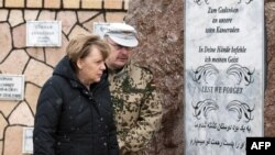 German Chancellor Angela Merkel (left) and Bundeswehr Commandant Erich Pfeffer in front of the memorial to fallen soldiers at the German base in Mazar-e Sharif on March 12.
