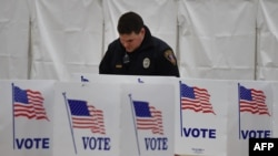 Сотрудник полиции готовится голосовать на участке в здании школы в Нью-Гэмпшире, США. 9 февраля 2016 года.