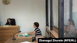 Акмарал Алмагамбетова (слева, за стеклянной перегородкой) в зале суде, где ей предъявлены обвинения в «пропаганде терроризма» и «возбуждении розни». Актобе, 22 июля 2019 года.