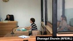 Акмарал Алмагамбетова (справа, за стеклянной перегородкой) в зале суде, где ей предъявлены обвинения в «пропаганде терроризма» и «возбуждении розни». Актобе, 22 июля 2019 года.