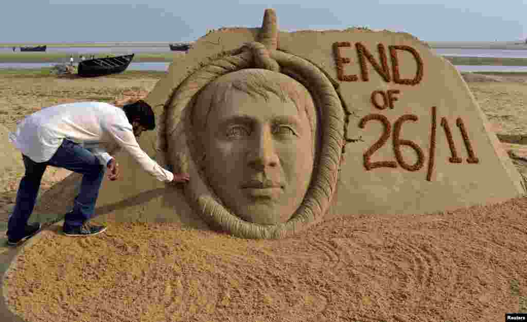 Indian sand artist Sudarshan Patnaik gives the final touches to a sand sculpture of Mohammad Ajmal Kasab, the lone survivor of the Pakistan-based militant squad responsible for a rampage through Mumbai that killed 166 people who was secretly hanged, on a beach in the eastern Indian state of Odisha. (Reuters)