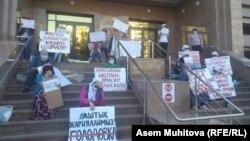 Объявившие голодовку с требованием выплат и жилья матери на молчаливом протесте с плакатами у входа в министерство труда и социальной защиты населения Казахстана. Нур-Султан, 9 июня 2020 года.