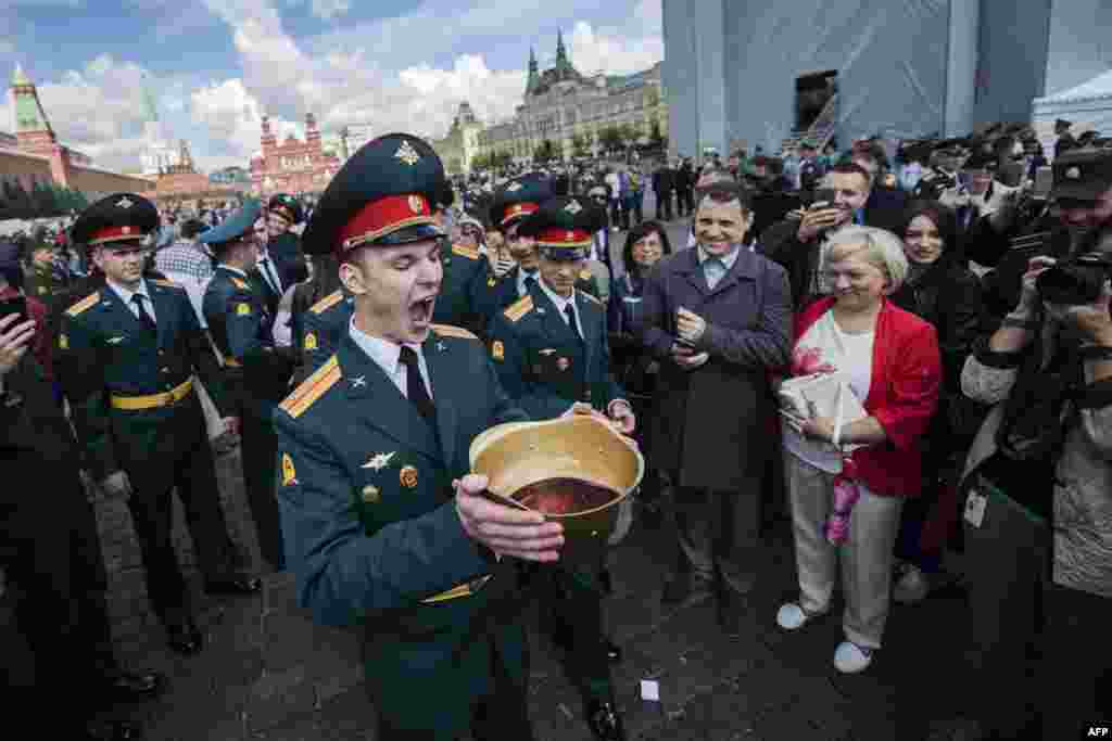 Graduates of the Moscow Military Commanders Training School drink sparkling wine from a helmet during their graduation ceremony in Red Square in Moscow. (AFP/Natalia Kolesnikova)