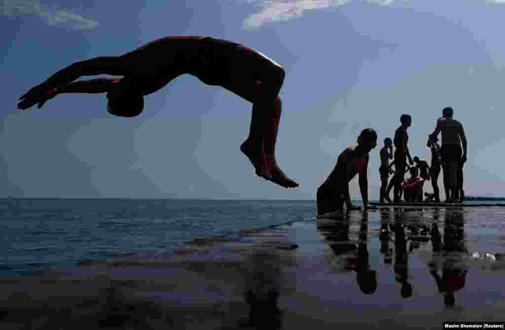 A boy jumps into the Black Sea from a pier in central Sochi, Russia, on June 30. (Reuters/Dmitry Serebryakov)