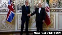 U.K. Foreign Secretary Philip Hammond (left) meets his Iranian counterpart Mohammad Javad Zarif in Tehran on August 23.