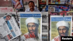 Pakistan -- A roadside vendor sells newspapers with headlines about the death of al-Qaeda leader Osama bin Laden, in Lahore, 03May2011