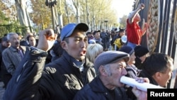 Kyrgyzstan -- Relatives of victims killed during a revolt in April, that drove former President Kurmanbek Bakiyev from office, protest near the gate of the parliament during its first session in Bishkek, 10Nov2010