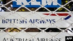 A picture taken on August 24, 2018 shows the logos of air line companies (top to bottom) Dutch KLM, British Airways, and Austrian Airlines, on the shuttered window of the closed offices of a travel agency in the Iranian capital Tehran. Air France and Brit