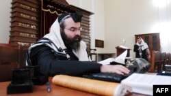 A man swathed in a tallit, or Jewish prayer shawl, reads a religious book at a synagogue in Baku. (file photo)