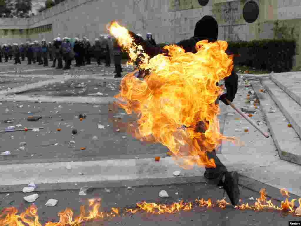 A Greek protester in Athens throws a petrol bomb at riot police during demonstrations on December 6 to mark the 2008 shooting of a student by police. (Photo for Reuters by Yannis Behrakis)