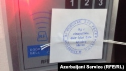 Azerbaijani prosecutors seal shut RFE/RL's Baku bureau after ordering staff to leave during a raid on December 26,2014.