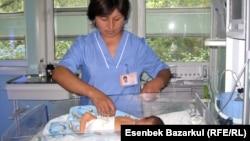 Жаңа туған нәрестеге қарап жатқан медбике. Алматы, 24 тамыз 2010 жыл. (Көрнекі сурет)