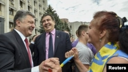 Ukrainian President Petro Poroshenko (left) and new Odesa Governor Mikheil Saakashvili are greeted by local residents near the regional state administration building in Odesa on May 30, 2015.