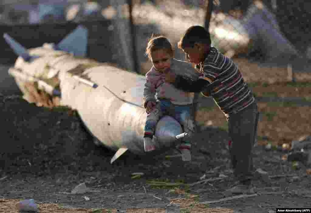A Syrian boy places another child on the tip of an abandoned missile at the Ash'ari camp for the displaced in the rebel-held eastern Ghouta area outside the capital Damascus. (AFP/Amer Almohibany)