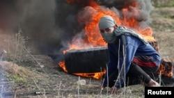 Газа қаласының шығыс бөлігінде Израиль әскерилерімен қақтығыс болып жатқан жерде жүрген палестиналық. 15 желтоқсан 2017 жыл.
