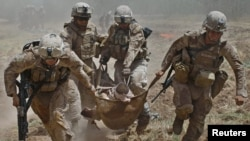 U.S. Marines carry a comrade wounded by an improvised explosive device near the town of Marjah in Helmand Province