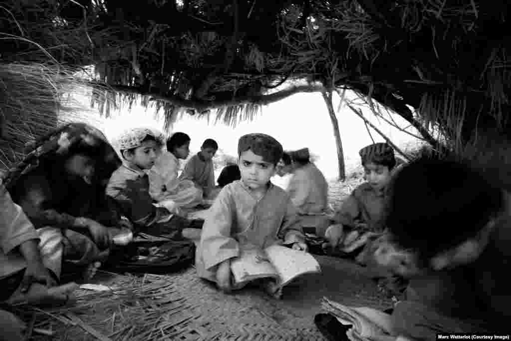 A child sits inside a makeshift school building built by Baloch refugees who fled the violence that engulfed their remote rural villages.