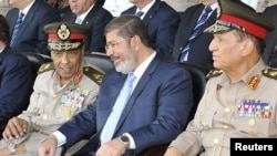 Egyptian President Muhammad Morsi (center) speaks with Field Marshal Hussein Tantawi (left) and Egyptian Armed Forces Chief Of Staff Sami Anan during a graduation ceremony at Cairo's military academy last month.