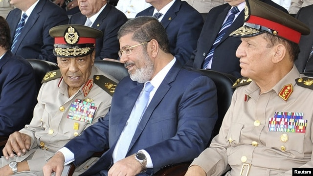 Egyptian President Muhammad Morsi (center) speaks with Hussein Tantawi (left) and Sami Anan during a ceremony in Cairo on July 17.