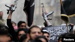 Люди с оружием и исламским флагом во время акции протеста против президента Сирии Башара Асада в районе Бустан аль-Каср. Алеппо, 22 марта 2013 года.