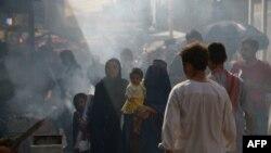 An Afghan burqa-clad woman carries a child on a busy market street in Mazar-i Sharif.