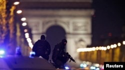 Masked police stand on top of their vehicle on the Champs-Elysees Avenue after the shooting late on April 20.