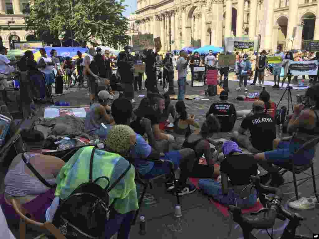 Акція протесту щодо обмеження фінансування поліції біля міської ратуші в Нью-Йорку продовжується, не зважаючи на зростання випадків захворювання COVID-19, хоча кількість учасників акції зменшилась. Волонтери роздавали учасникам маски, дезінфікуючі засоби, продукти харчування та напої. Поліцейські стояли поруч і не втручалися