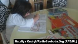 Римська першокласниця вдома за уроками