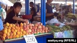 Көк базарда жеміс-жидек сатып тұрған сатушы. Алматы, 17 шілде 2013 жыл.