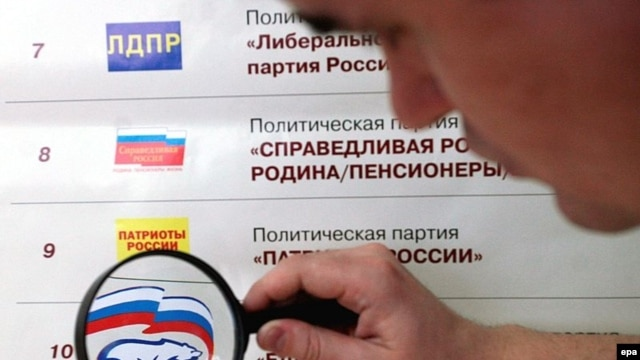A man looks at the logo of the pro-presidential United Russia party showed among others on the election poster at a polling station in Kemerovo.