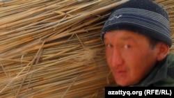 Алтынбек Ибрашев, житель села Белкопа, несет вязанку камыша, 19 февраля 2012 года.