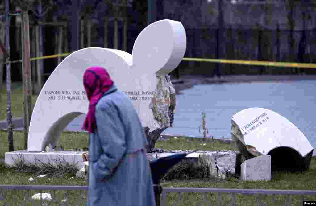 A woman walks past a destroyed monument in the southern Bosnian city of Mostar, 100 kilometers from the capital, Sarajevo. A bomb blast destroyed the monument to fallen soldiers of Bosnia's Muslim-dominated wartime army in Mostar, where divisions between ethnic Croats and Muslims still run deep. (Reuters/Dado Ruvic)