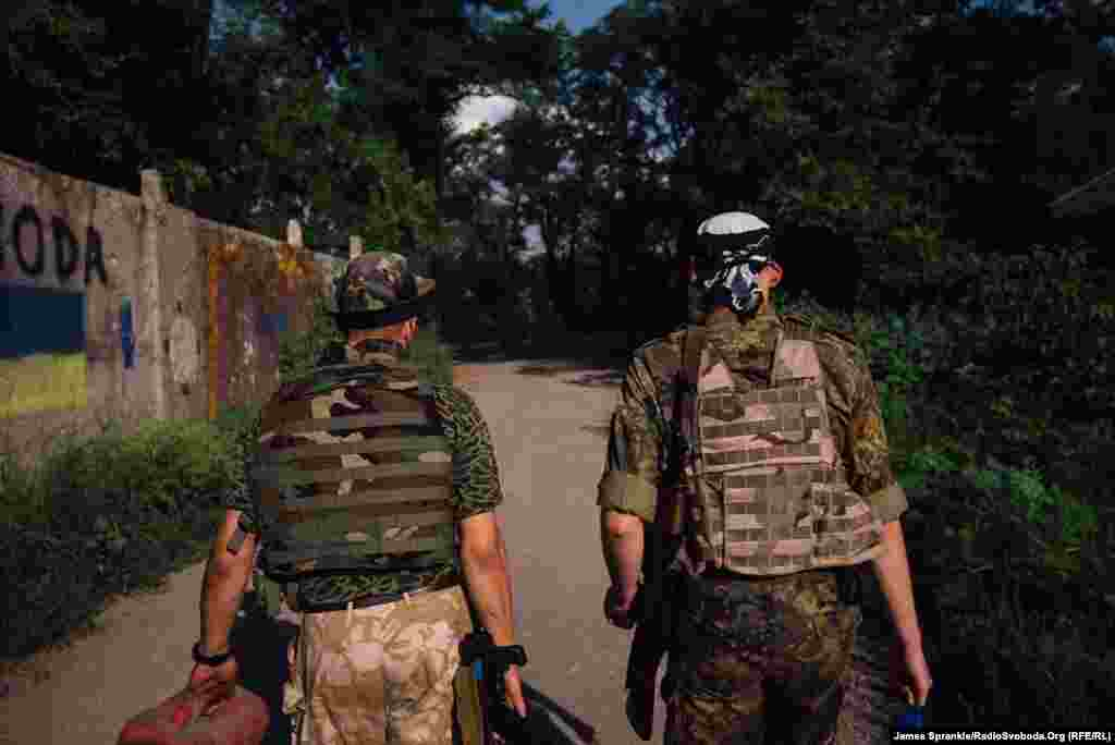 Dan and Chemist, from the 93rd Brigade, walk toward their front line positions, where they will spend the next few hours observing enemy positions in Donetsk.