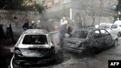 Пожарный обливает автомобиль, который загорелся после минометного обстрела. Дамаск, 26 марта 2013 года.