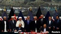 While the chief executive of the Afghan government Abdullah Abdullah (fourth from left) and President Ashraf Ghani (fourth from right) look on, Afghan National security adviser Hanif Atmar (at table,right) and U.S. Ambassador James Cunningham sign a bilateral security agreement in Kabul on September 30.